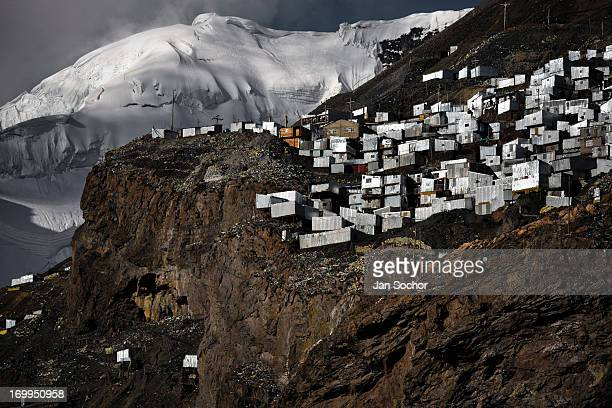 Corrugated metal shacks homes of gold miners seen on a steep mountainside under a glacier in La Rinconada Peru 3 August 2012 During the last decade...