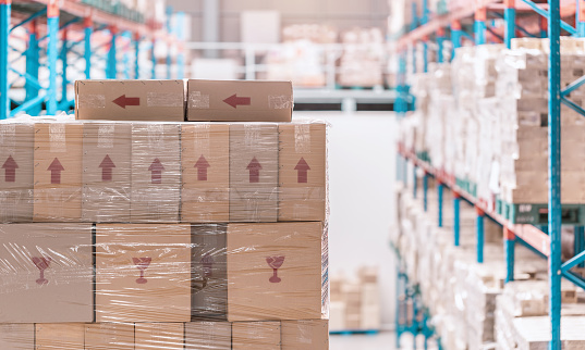 corrugated paperboard carton stacked on shelf in warehouse or depot 1144176218