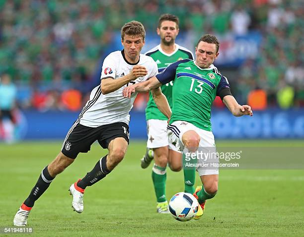 Corry Evans of Northern Ireland and Thomas Mueller of Germany compete for the ball during the UEFA EURO 2016 Group C match between Northern Ireland...