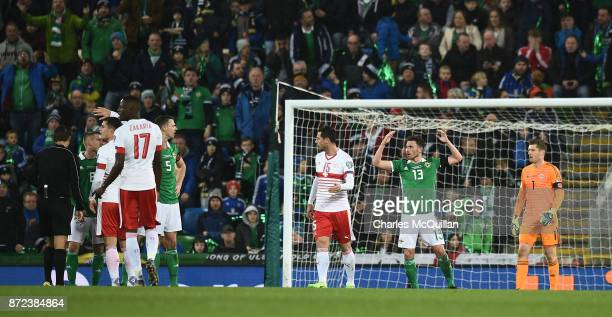 Corry Evans of Northern Ireland concedes a controversial penalty after a handball following a shot from Xherdan Shaqiri of Switzerland during the...