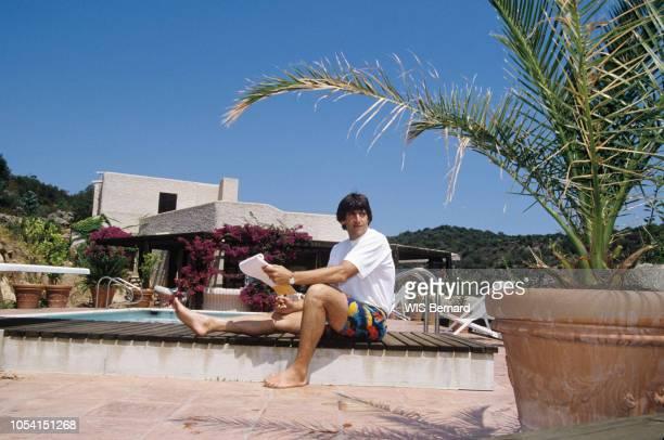 Corse Juillet 1990 Le chanteur Yves DUTEIL en vacances dans sa maison en Corse Ici assis au bord de sa piscine un carnet et un stylo à la main
