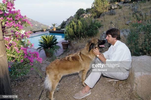 Corse Juillet 1990 Le chanteur Yves DUTEIL en vacances dans sa maison en Corse Ici assis dans son jardin face à sa chienne Leonberg Eulalie sa...