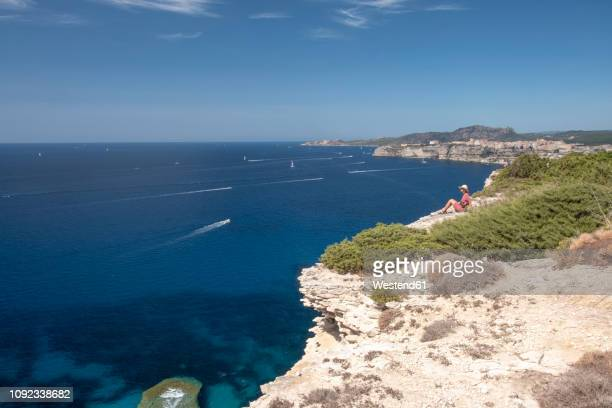 corsica, mediterranean coast, woman sitting on rocky cliff - corsica photos et images de collection