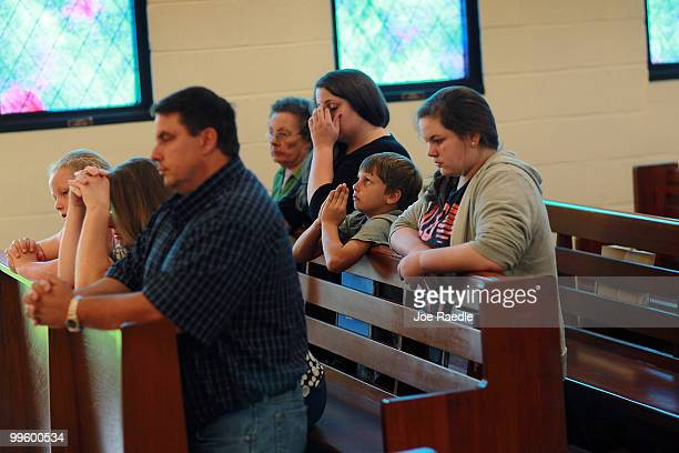 Cort Johnson prays along with his father Sean Johnson who owns a seafood processiong business and the rest of the family at the Saint Michael's...