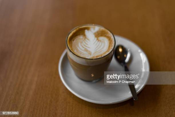 cortado espresso based coffee drink, served in glass with foam latte art - espresso stock photos and pictures