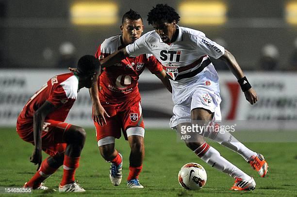 Cortez of Brazil's Sao Paulo, vies for the ball with Armando Gomez and Jesus Alcivar of Ecuador's Liga de Loja, during their 2012 Copa Sudamericana...