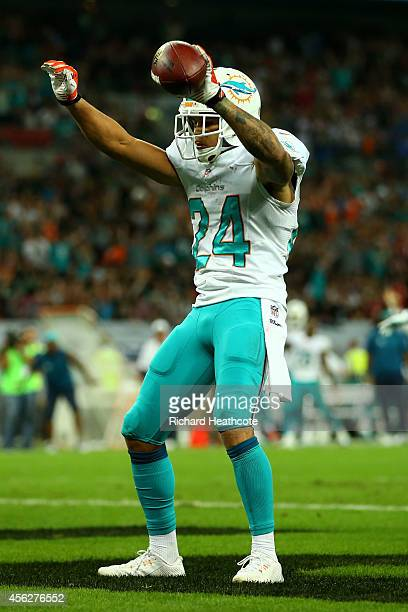 Cortland Finnegan of the Miami Dolphins celebrates after returning a fumble 50 yards to score a touchdown during the NFL match between the Oakland...
