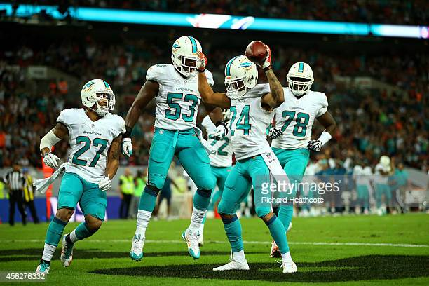 Cortland Finnegan of the Miami Dolphins celebrates with teammates after returning a fumble 50 yards to score a touchdown during the NFL match between...