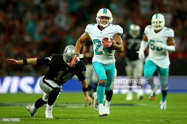 Cortland Finnegan of the Miami Dolphins returns a fumble 50 yards to score a touchdown during the NFL match between the Oakland Raiders and the Miami...