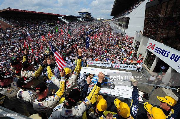 Corvette C6R drivers Johnny O'Connell of the US Antonio Garcia of Spain and Jan Magnussen of Denmark celebrate the GT1 class victory with Corvette...