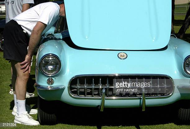 A Corvette enthusiast looks into the hood of a 1957 roadster on display at the Bloomington Gold Corvette show 27 June 2003 in St Charles IL The...