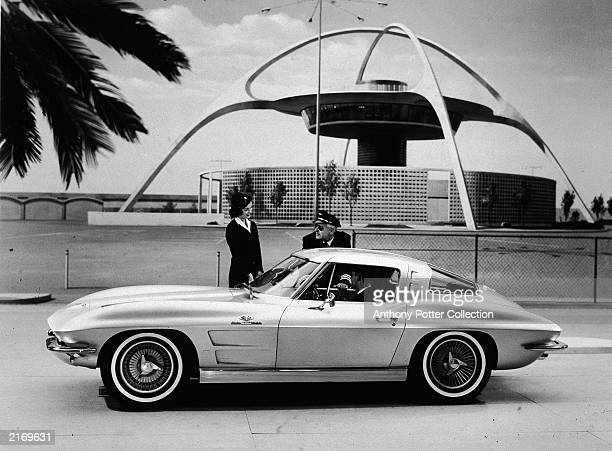 Corvette Sting Ray Sport Coupe is admired by a pilot and flight attendant at at Los Angeles Airport , c. 1962.
