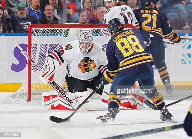 Cory Conacher of the Buffalo Sabres moves in on goaltender Corey Crawford of the Chicago Blackhawks on March 9 2014 at the First Niagara Center in...
