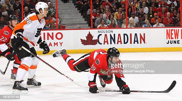 Cory Conacher of the Ottawa Senators falls to the ice as Oliver Lauridsen of the Philadelphia Flyers looks on during an NHL game at Scotiabank Place...