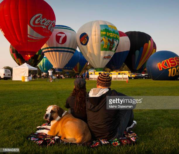 """Cory Doman, right, Denise Shirts and their dog """"Tank"""" admire the spectacle of balloons as they fill with hot air at Ann Morrison Park in Boise,..."""