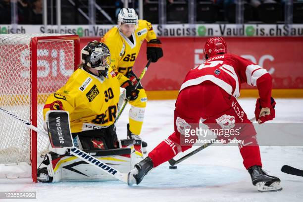 Cory Emmerton of Lausanne HC tries to score against Goalie Philip Wuthrich of SC Bern in front of Ramon Untersander of SC Bern during the Swiss...