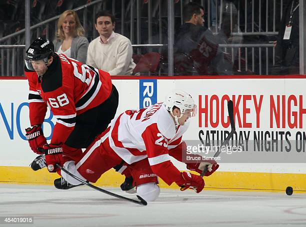 Cory Emmerton of the Detroit Red Wings is tripped up by Jaromir Jagr of the New Jersey Devils during the first period at the Prudential Center on...