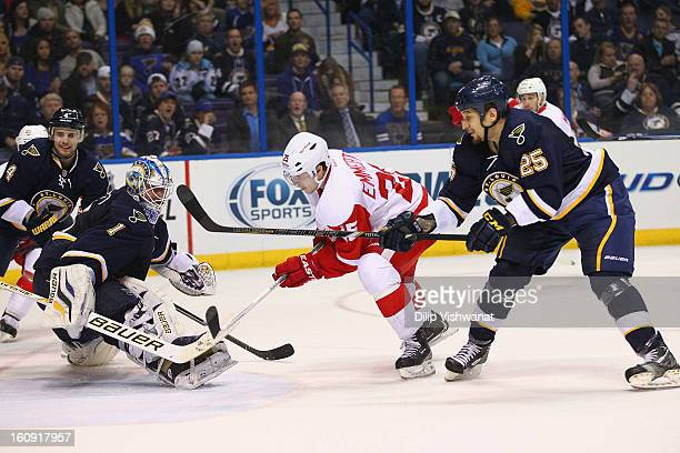 Cory Emmerton of the Detroit Red Wings scores a goal against Chris Stewart and Brian Elliott both of the St Louis Blues at the Scottrade Center on...