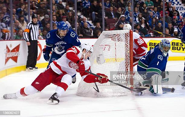 Cory Emmerton of the Detroit Red Wings tries a wraparound on goalie Roberto Luongo during the second period in NHL action on December 21 2011 at...