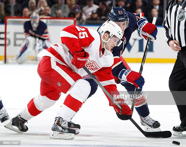 Cory Emmerton of the Detroit Red Wings wins a faceoff against the New York Rangers at Madison Square Garden on January 16 2014 in New York City The...
