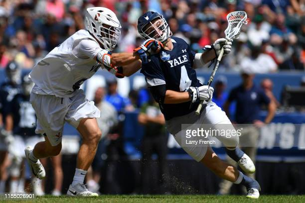 Cory Harris of the Virginia Cavaliers checks John Daniggelis of the Yale Bulldogs during the Division I Men's Lacrosse Championship held at Lincoln...
