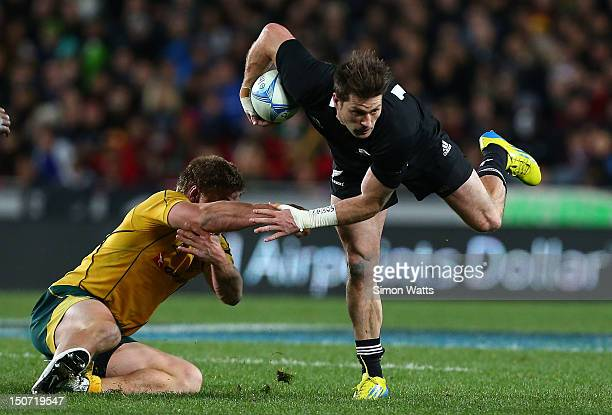 Cory Jane of the All Blacks beats the tackle of Michael Hooper of the Wallabies during The Rugby Championship Bledisloe Cup match between the New...