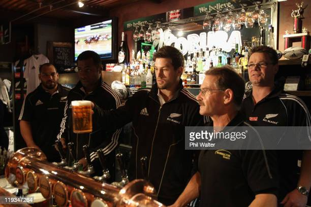Cory Jane of the All Blacks delivers a pint for a punter at the Mornington Tavern watched by John Afoa and Sitiveni Sivivatu on July 19 2011 in...
