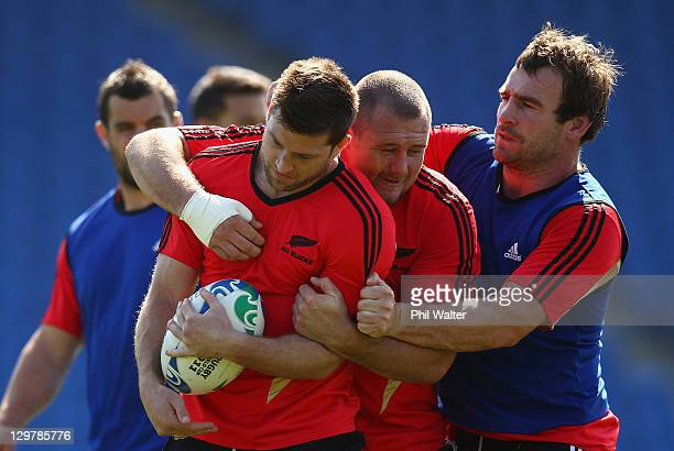 Cory Jane of the All Blacks is held by Tony Woodcock and Andrew Hore during a New Zealand All Blacks training session at Trusts Stadium on October 21...