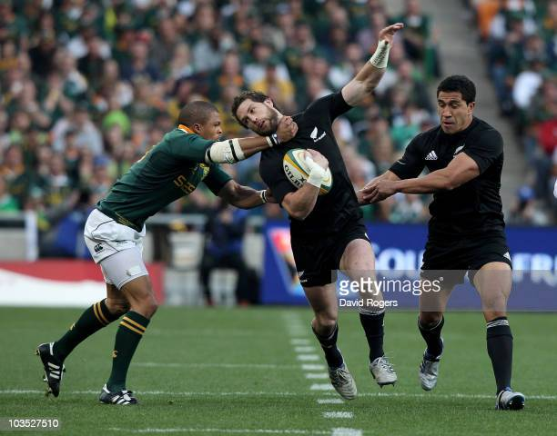 Cory Jane of the All Blacks is high tackled by Juan de Jongh during the 2010 TriNations match between the South African Springboks and the New...