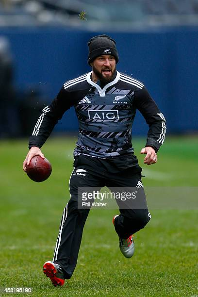 Cory Jane of the All Blacks runs with a NFL football during the New Zealand All Blacks Captain's run at Soldier Field on October 31 2014 in Chicago...