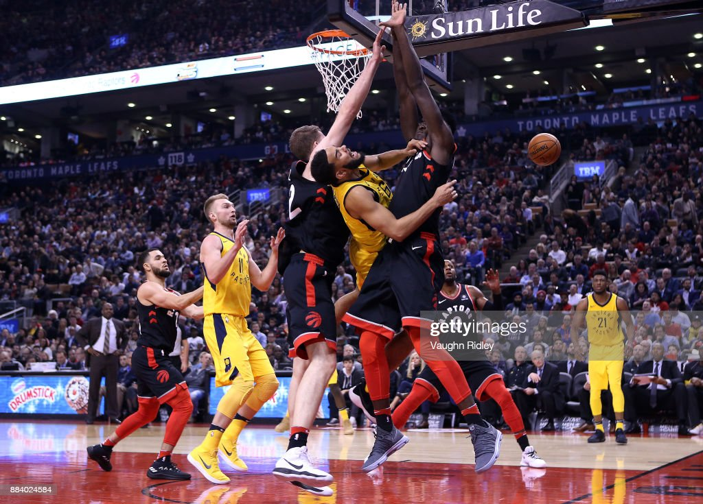 Cory Joseph #6 of the Indiana Pacers passes the ball as Jakob Poeltl #42 and Pascal Siakam #43 of the Toronto Raptors defend during the first half of an NBA game at Air Canada Centre on December 1, 2017 in Toronto, Canada.