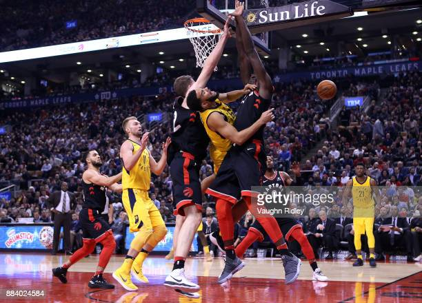 Cory Joseph of the Indiana Pacers passes the ball as Jakob Poeltl and Pascal Siakam of the Toronto Raptors defend during the first half of an NBA...