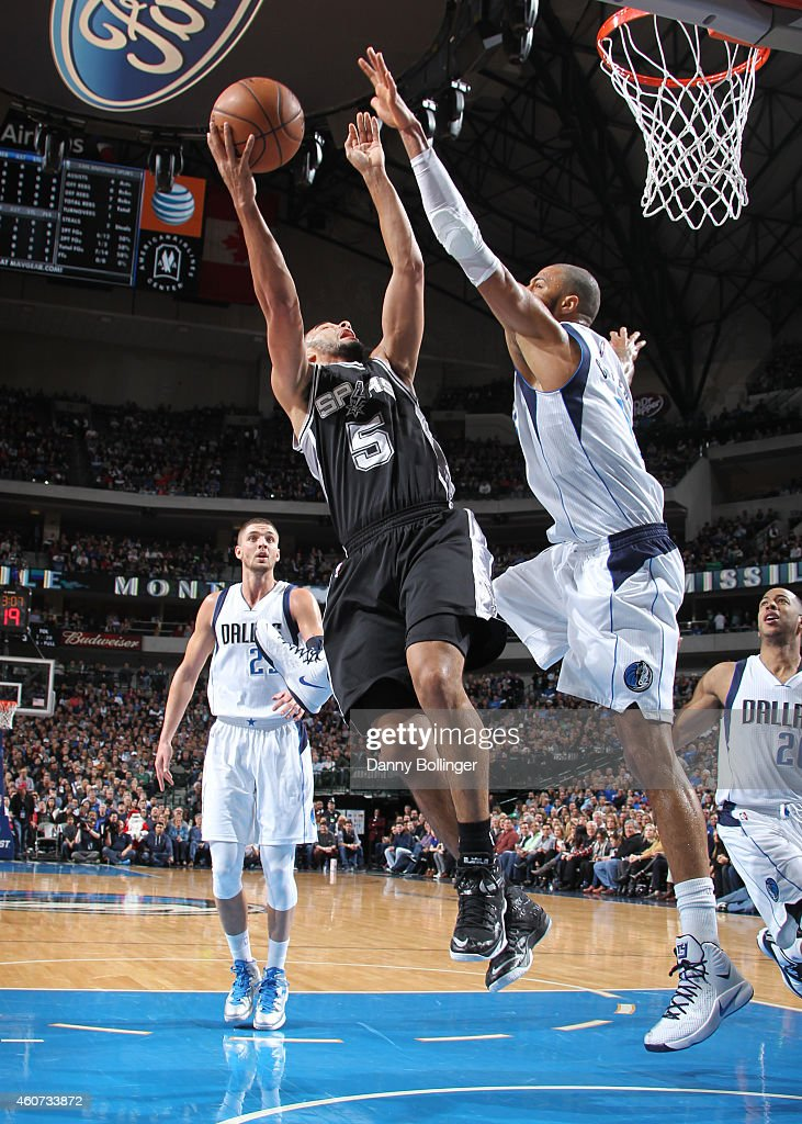 Cory Joseph #5 of the San Antonio Spurs goes in for the layup against Tyson Chandler #6 of the Dallas Mavericks on December 20, 2014 at the American Airlines Center in Dallas, Texas.