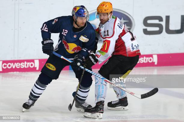 Cory Quirk of Pinguins Bremerhaven vies Mads Christensen of Red Bull Munich during the DEL playoff match between the EHC Red Bull Munich and Pinguins...