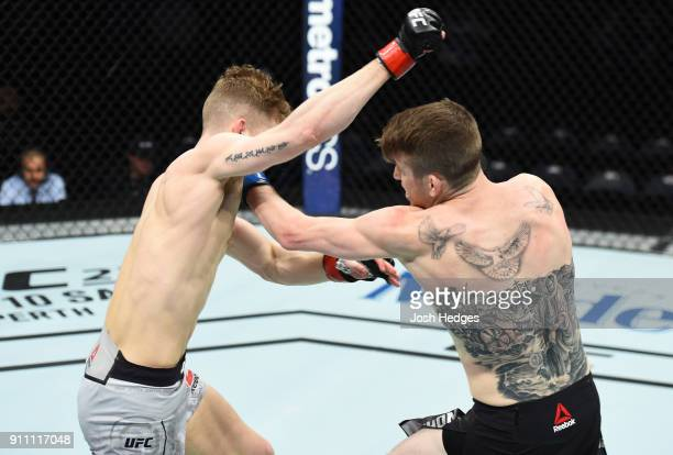 Cory Sandhagen punches Austin Arnett in their featherweight bout during a UFC Fight Night event at Spectrum Center on January 27 2018 in Charlotte...