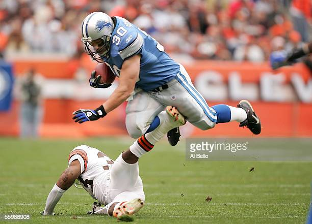 Cory Schlesinger of the Detroit Lions runs with the ball as Daylon McCutcheon makes the tackle on October 23, 2005 at Cleveland Browns Stadium in...