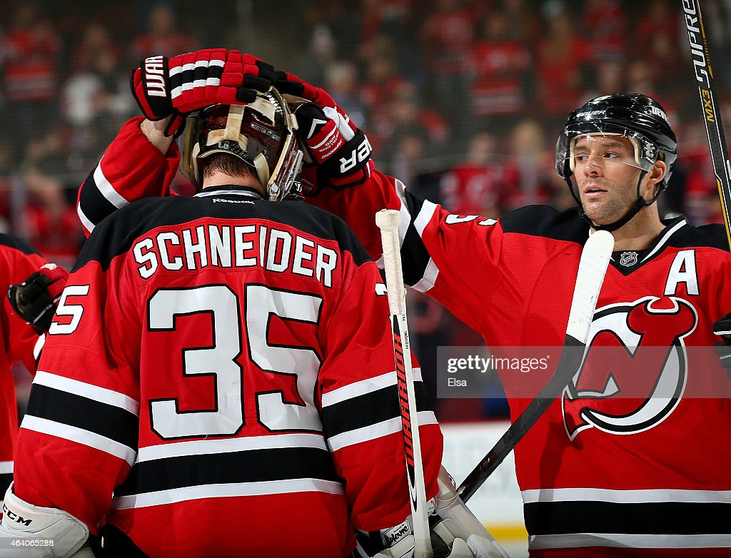 Cory Schneider #35 is congratulated by teammate Andy Greene #6 of the New Jersey Devils after the win over the Vancouver Canucks on February 20, 2015 at the Prudential Center in Newark, New Jersey.The New Jersey Devils defeated the Vancouver Canucks 4-2.