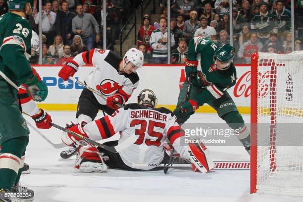 Cory Schneider makes a save as his New Jersey Devils teammate Will Butcher defends against Joel Eriksson Ek of the Minnesota Wild during the game at...