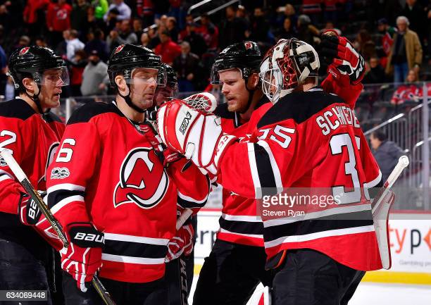Cory Schneider of the New Jersey Devils is congratulated by his teammates after his team defeated the Buffalo Sabres at Prudential Center on February...