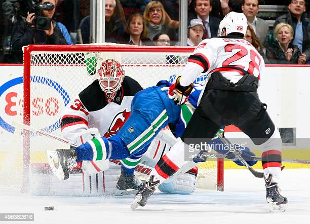 Cory Schneider of the New Jersey Devils keeps an eye on the puck despite activity in front of him during their NHL game against the Vancouver Canucks...