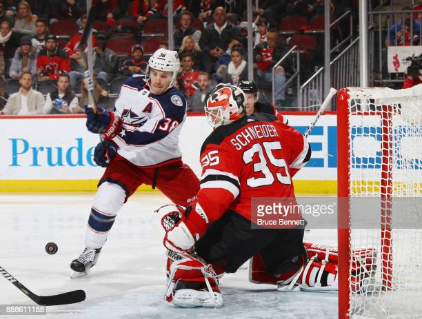 Cory Schneider of the New Jersey Devils kicks out a third period shot as Boone Jenner of the Columbus Blue Jackets looks for the rebound at the...
