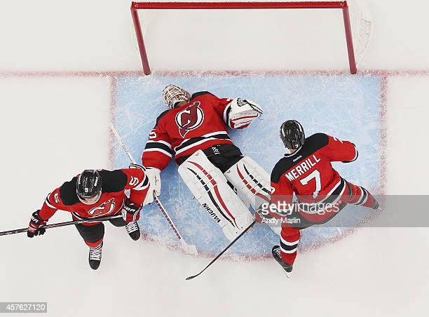 Cory Schneider of the New Jersey Devils lays the ice after being interfered with by Rick Nash of the New York Rangers during the game at the...