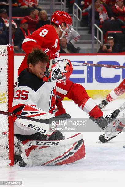 Cory Schneider of the New Jersey Devils loses his helmet next to Justin Abdelkader of the Detroit Red Wings during the second period at Little...