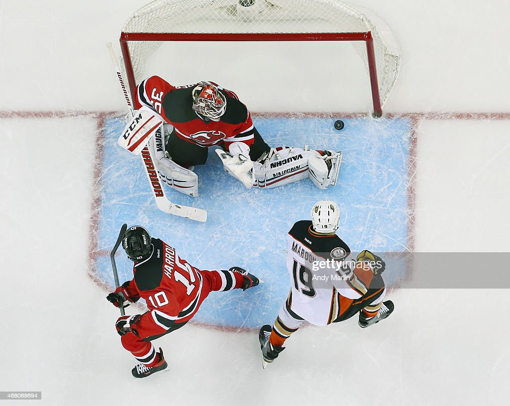 Cory Schneider #35 of the New Jersey Devils makes a save against Patrick Maroon #19 of the Anaheim Ducks as Peter Harrold #10 defends during the game at the Prudential Center on March 29, 2015 in Newark, New Jersey.