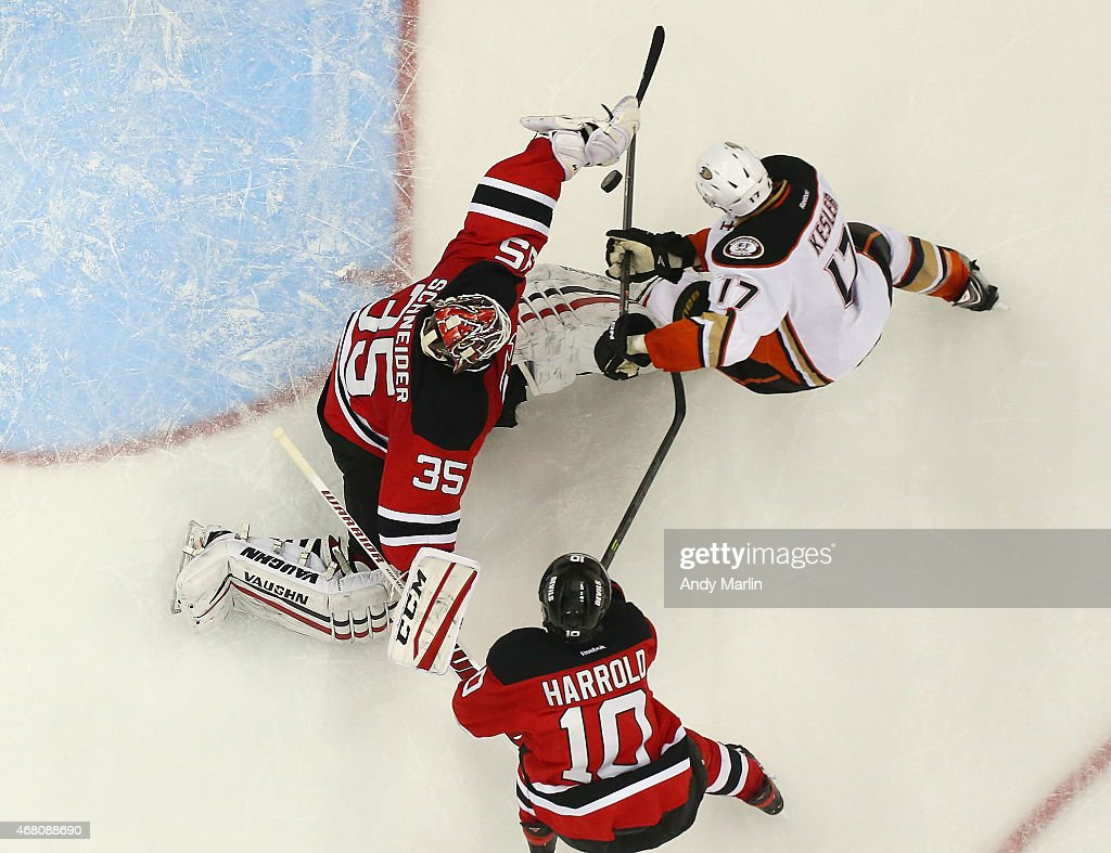 Cory Schneider #35 of the New Jersey Devils makes a save against Ryan Kesler #17 of the Anaheim Ducks as Peter Harrold #10 defends during the game at the Prudential Center on March 29, 2015 in Newark, New Jersey.