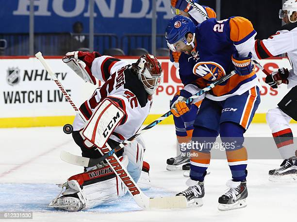 Cory Schneider of the New Jersey Devils makes a save against Stephen Gionta of the New York Islanders during their pre season game at Barclays Center...