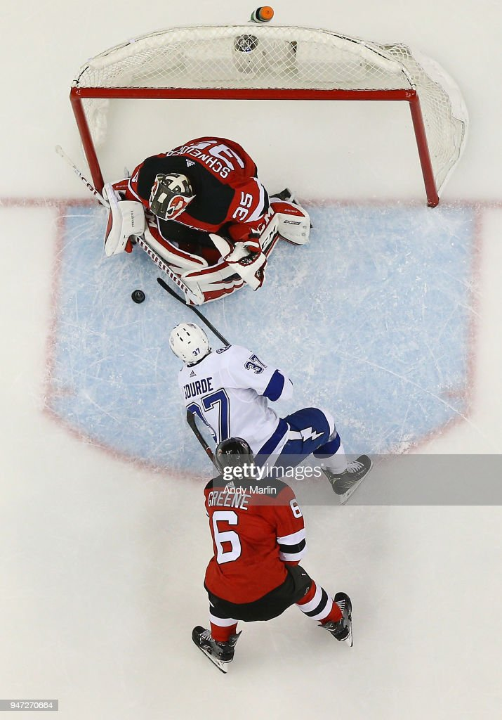 Cory Schneider #35 of the New Jersey Devils makes a save on a close in shot by Yanni Gourde #37 as Andy Greene #6 looks on in Game Three of the Eastern Conference First Round against the Tampa Bay Lightning during the 2018 NHL Stanley Cup Playoffs at Prudential Center on April 16, 2018 in Newark, New Jersey. The Devils defeated the Lightning 5-2.