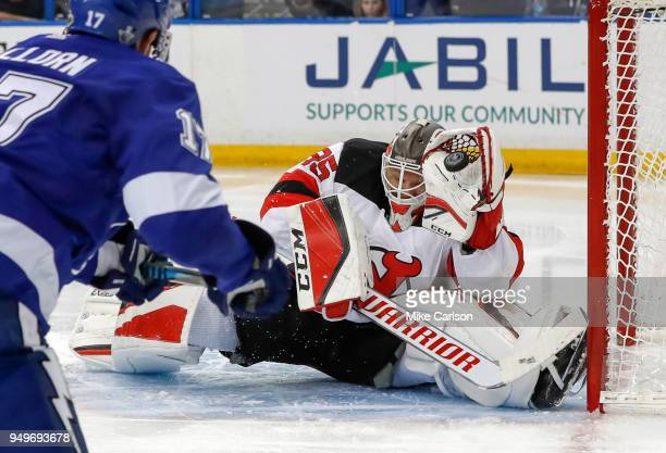 Cory Schneider of the New Jersey Devils makes a save on Alex Killorn of the Tampa Bay Lightning in the second period of Game Five of the Eastern...