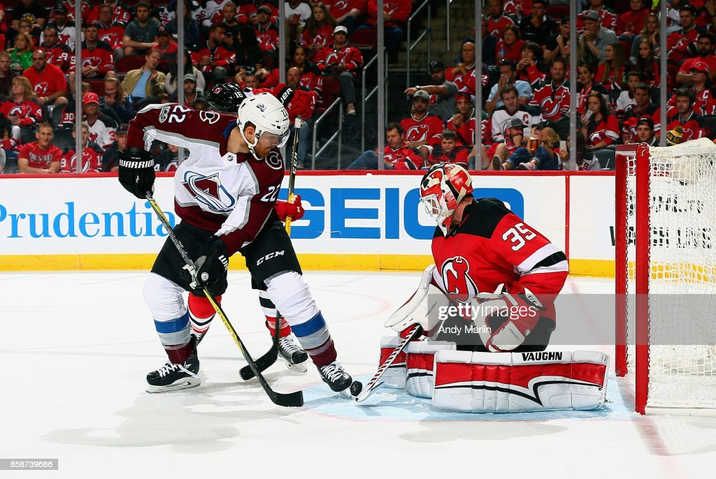 Cory Schneider #35 of the New Jersey Devils makes a stick save as Colin Wilson #22 of the Colorado Avalanche looks for the rebound during the Devils season opener at Prudential Center on October 7, 2017 in Newark, New Jersey.