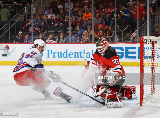 Cory Schneider of the New Jersey Devils makes the first period save on Brendan Smith of the New York Rangers at the Prudential Center on December 21...